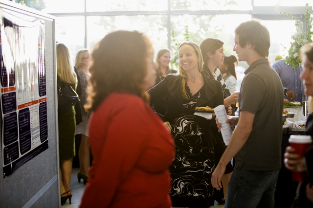 Sarah Lynne-Landsman (center), Ph.D., assistant professor and ICHP faculty, discusses her research with the event's attendees as the sun sets behind the Clinical and Translational Science Building.