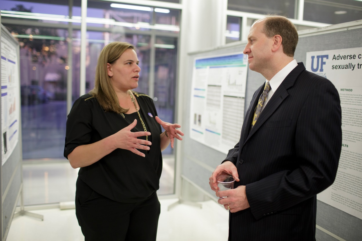 Gina Eubanks, a doctoral student in the Department of Health Outcomes and Policy, discusses her research with Bill Hogan, M.D., M.S., at ICHP's annual research event in November.