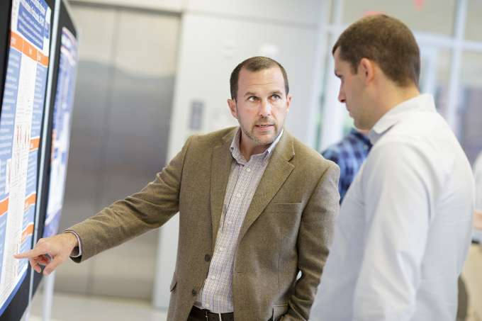Chris Delcher, Ph.D., assistant professor in the Department of Health Outcomes & Policy, explains his prescription drug related research to Dominick Lemas, Ph.D., research assistant professor in the Department of Health Outcomes & Policy.