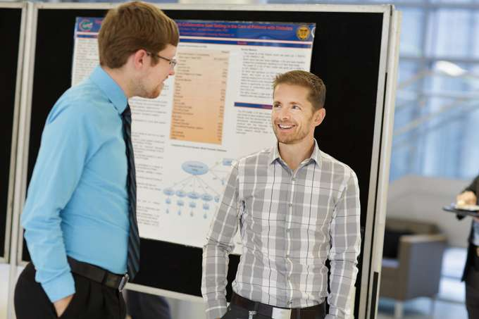 François Modave, Ph.D. (right), associate professor in the Department of Health Outcomes & Policy, talks with Jason Lee about the abundance of research featured at the 2015 ICHP Annual Research Day.