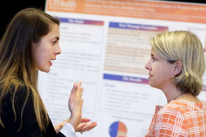Kristin Dayton, M.D. (left), a pediatric resident at UF Health, and Lindsay Thompson, M.D., assistant director of clinical research in the Institute for Child Health Policy, discuss the research the two conducted on heath care texting and its ability to positively affect the health of overweight and obese adolescents.